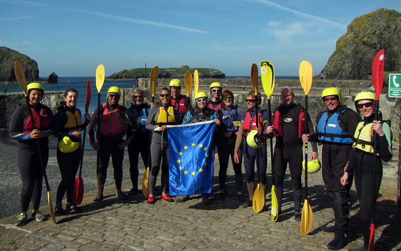 People stand in a harbour with kayak oars and wetsuits