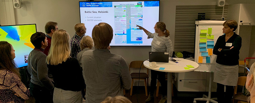 People discuss slides on a screen at the Helsinki workshop